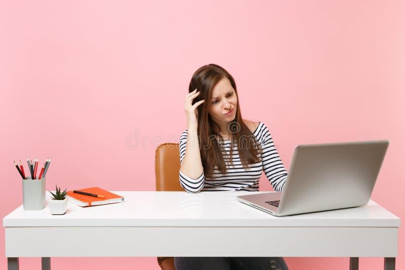 Menina confundida nova que mantém a mão na cabeça que trabalha no projeto ao sentar-se no escritório com o portátil do PC isolado fotos de stock royalty free