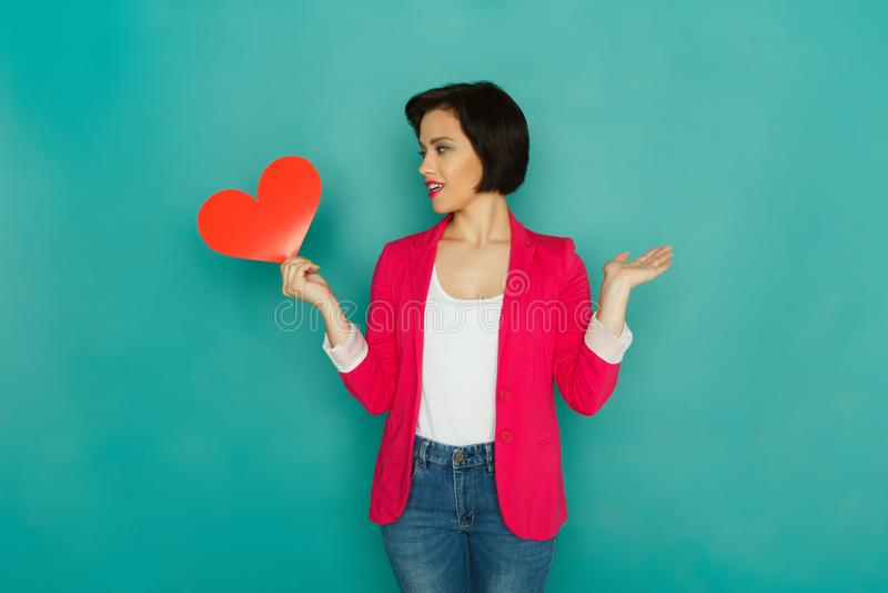 Menina confusa com coração de papel no fundo do estúdio fotos de stock royalty free