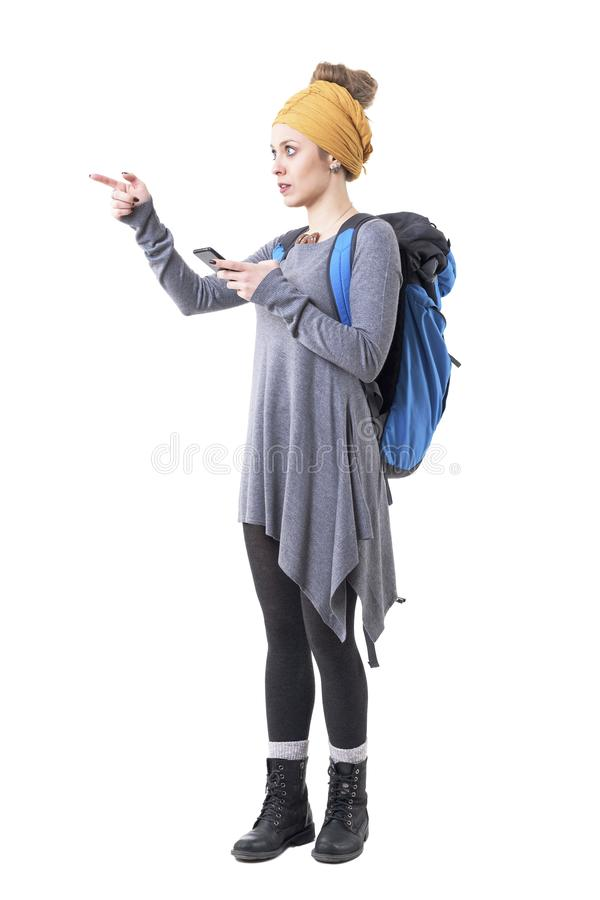 Menina confusa nova do moderno com a trouxa que mostra sentidos usando o mapa esperto da navegação do telefone foto de stock royalty free