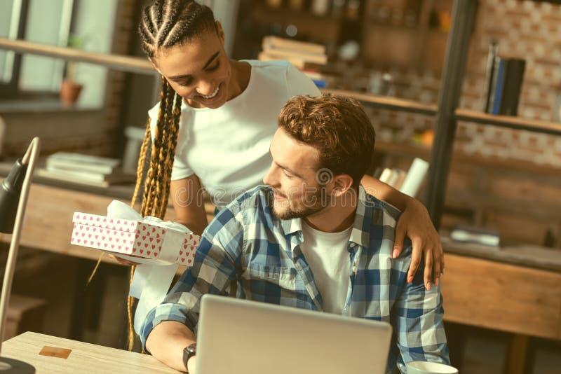 A menina consciente que dá seu noivo envolveu belamente o presente fotografia de stock royalty free
