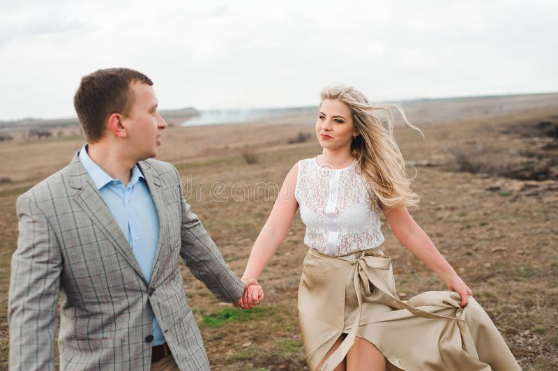 A menina considerável do indivíduo e do louro que anda no campo, um homem conduz uma mulher que guarda a mão imagem de stock royalty free