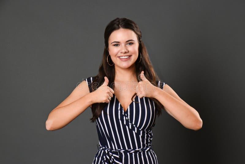 A menina consideravelmente adolescente com um sorriso bonito olha a câmera e dá dois polegares acima fotos de stock