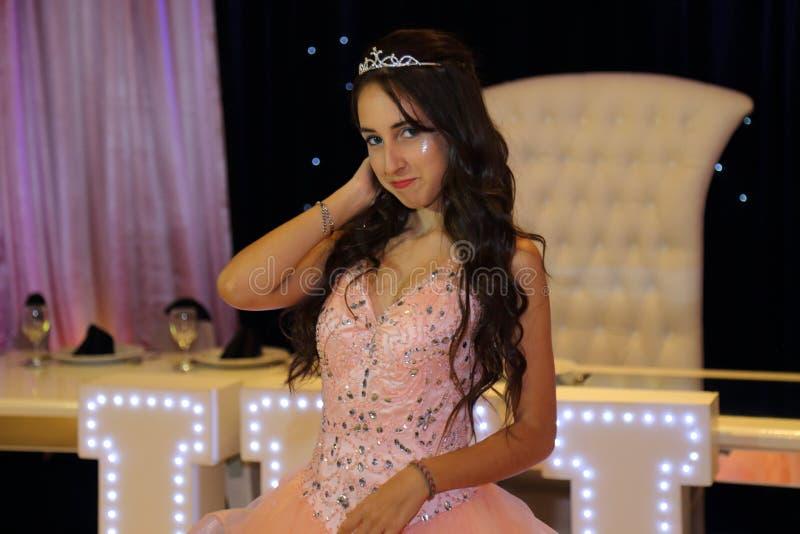 Menina consideravelmente adolescente do aniversário do quinceanera que comemora no partido do rosa do vestido da princesa, celebr fotografia de stock