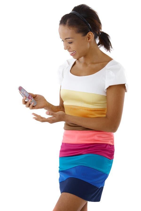 Menina consideravelmente afro que usa o telefone móvel fotografia de stock royalty free