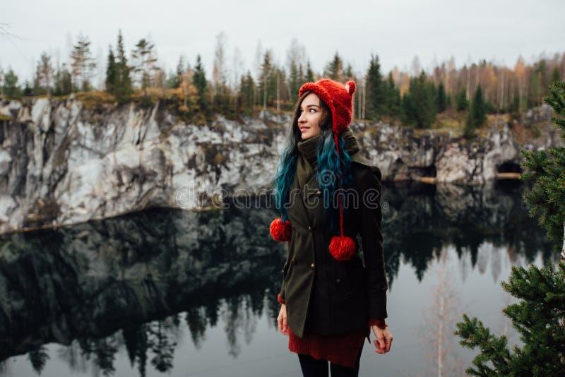 A menina consideravelmente agradável aprecia a opinião bonita do lago do hilltopl e o bom tempo em Carélia Em torno das rochas imagens de stock