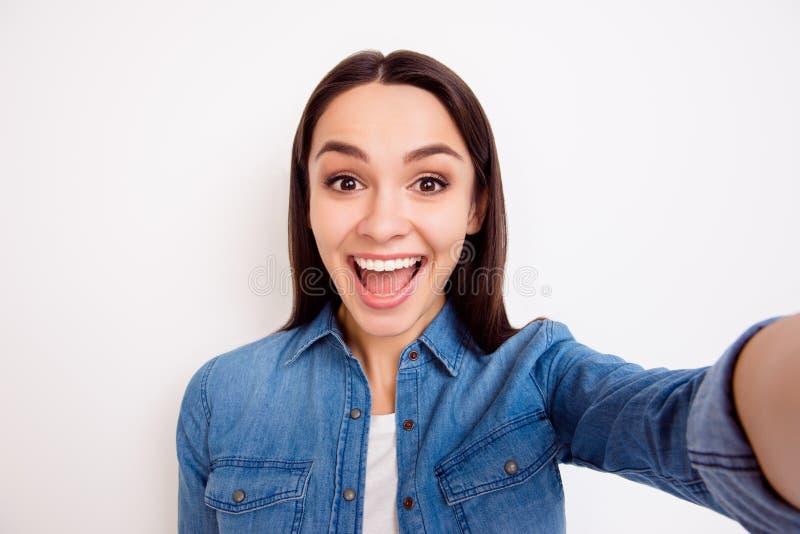 Menina consideravelmente alegre dos jovens na camisa das calças de brim que toma o autorretrato foto de stock royalty free