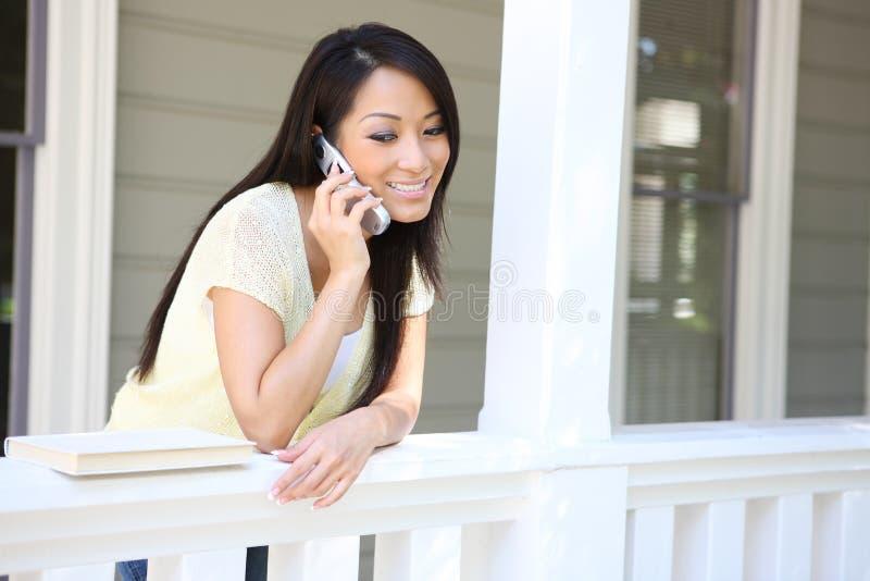 Menina consideravelmente asiática no telefone em casa foto de stock