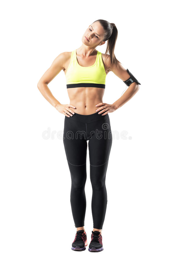 Menina consideravelmente desportiva na camiseta de alças amarela que faz a rotação principal do pescoço que aquece o exercício foto de stock