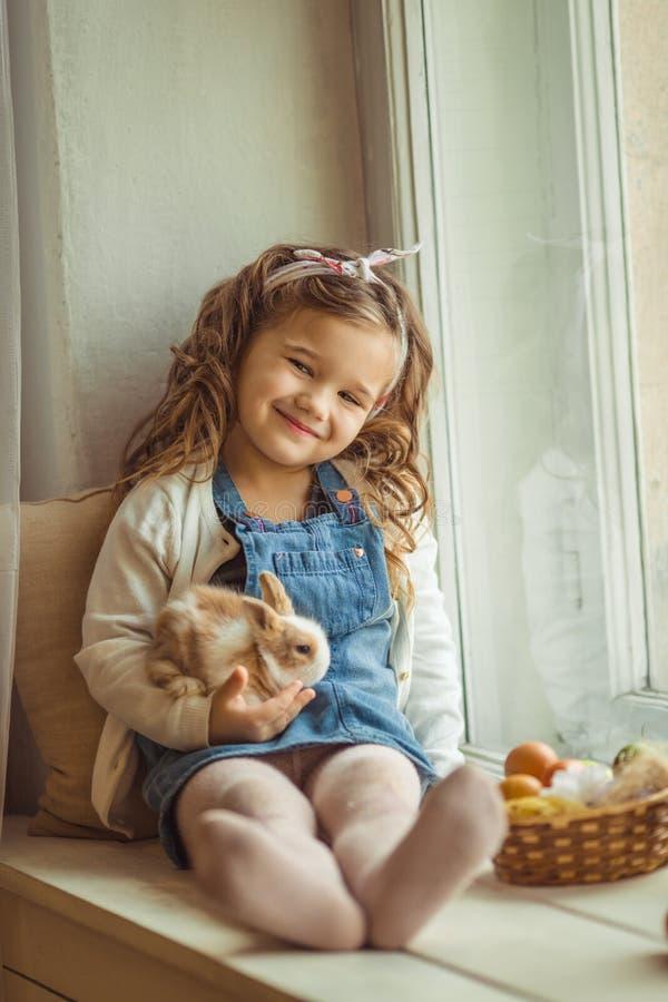 A menina consideravelmente feliz da criança está sentando-se no peitoril com seu coelho colorido pequeno do amigo, conceito da ja fotografia de stock royalty free