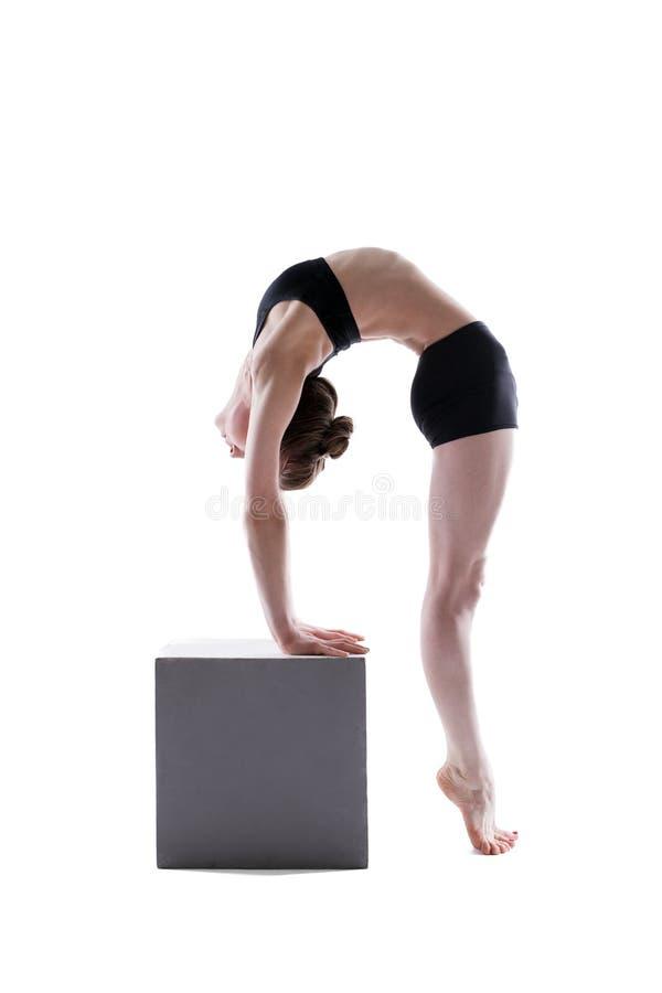 Menina consideravelmente flexível que levanta no cubo no estúdio fotos de stock royalty free