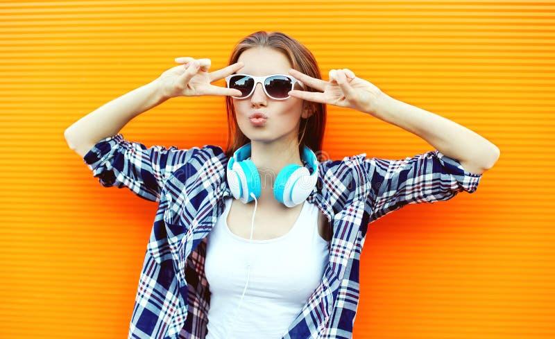 Menina consideravelmente fresca nos óculos de sol e nos fones de ouvido que têm o divertimento fotos de stock royalty free