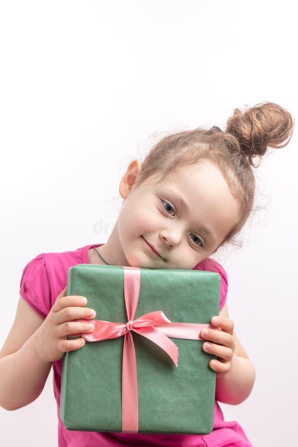 Menina consideravelmente impressionante que guarda sua cabeça no presente da caixa fotografia de stock
