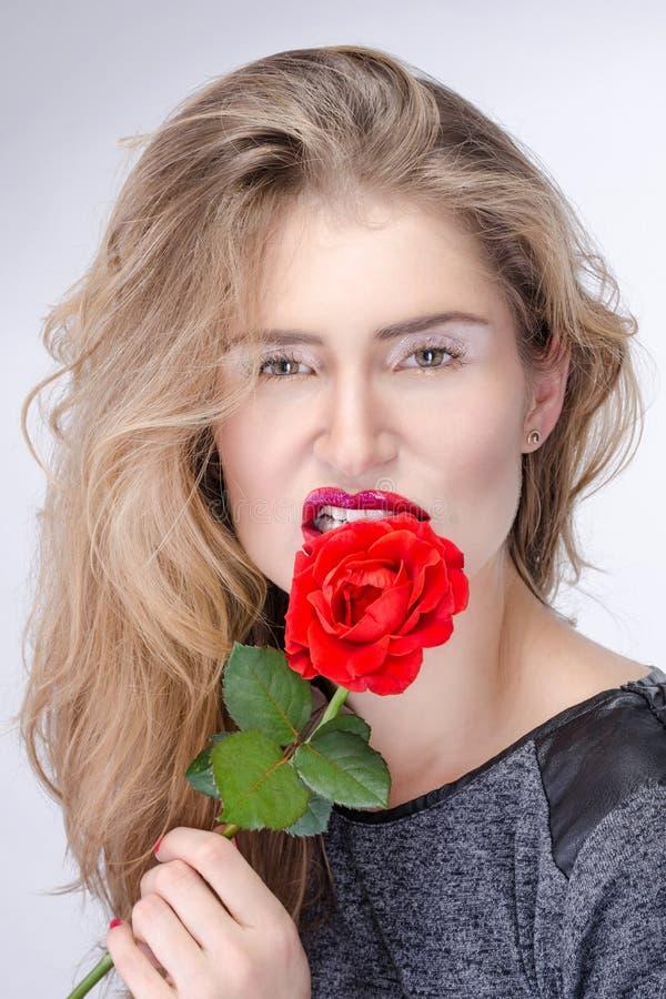 Menina consideravelmente loura com composição brilhante que morde uma flor imagem de stock
