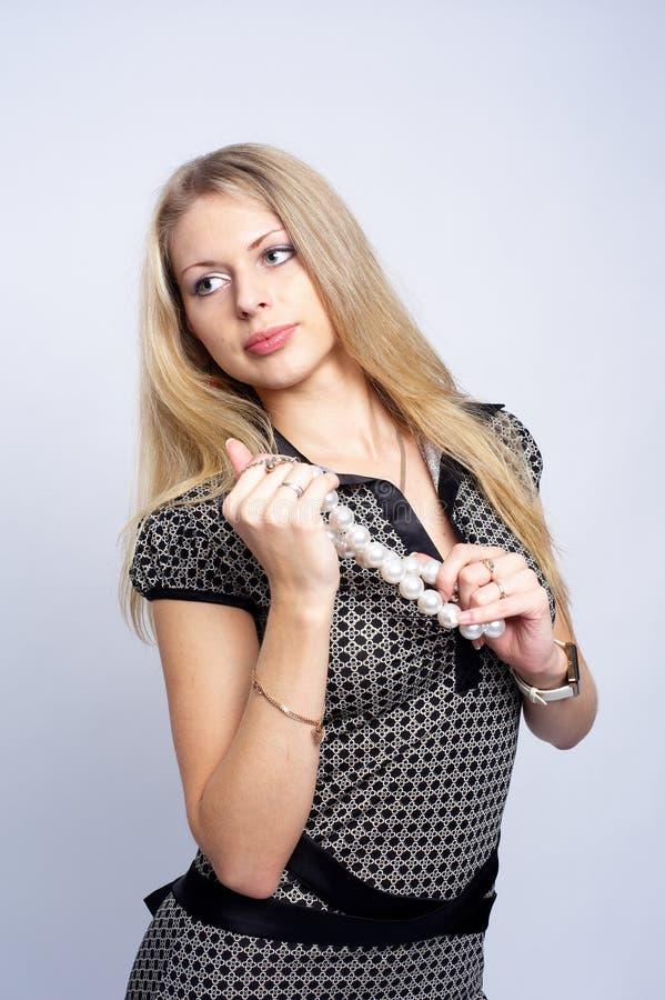 Menina consideravelmente loura com grânulos imagem de stock