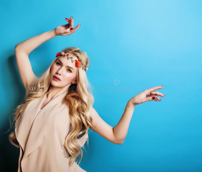Menina consideravelmente loura dos jovens com cabelo louro encaracolado e sorriso feliz das flores pequenas no fundo do céu azul, fotografia de stock royalty free