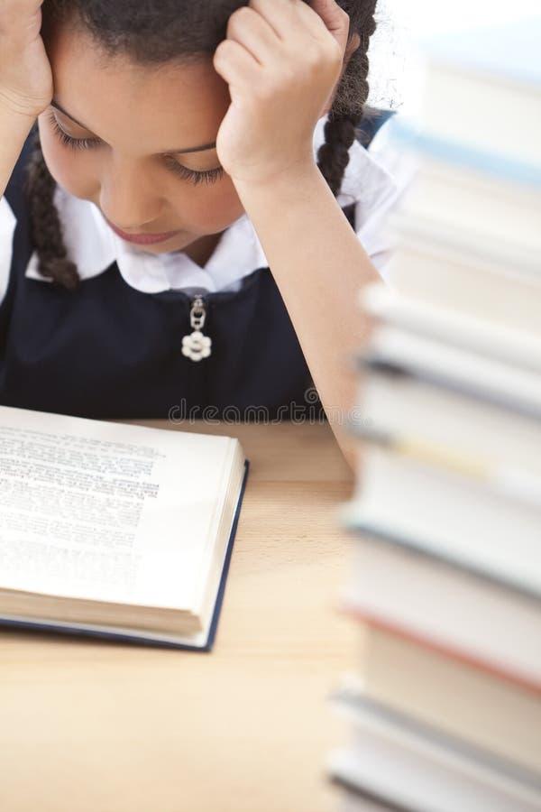 Menina consideravelmente nova da escola que lê um livro fotografia de stock royalty free
