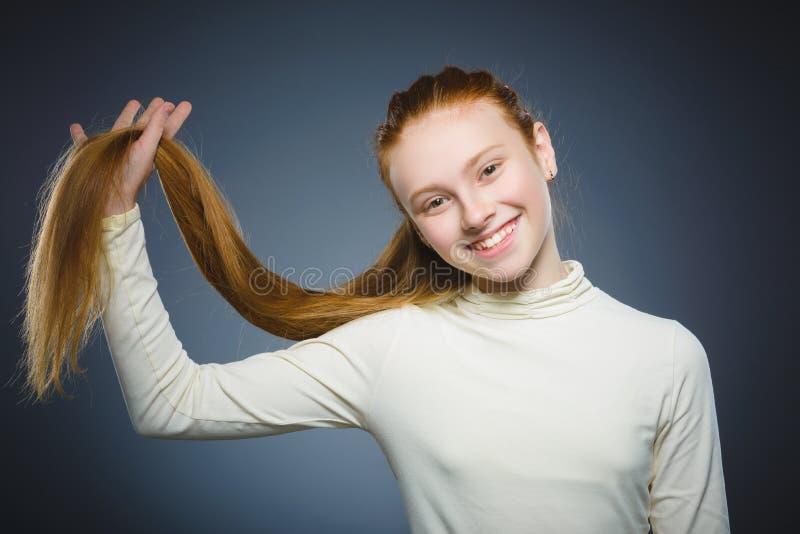 Menina consideravelmente ruivo que joga com seu cabelo isolado no cinza imagem de stock