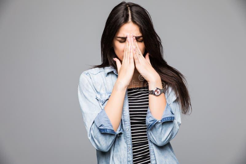 Menina consideravelmente triste que cobre sua cara ao gritar sobre o fundo cinzento foto de stock royalty free
