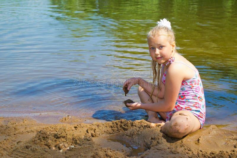A menina constrói um castelo da areia fotos de stock royalty free