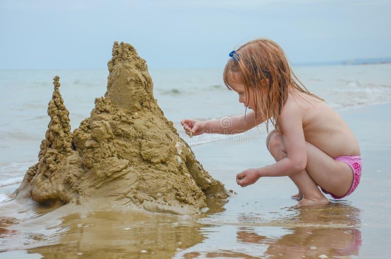 A menina constrói um castelo da areia foto de stock