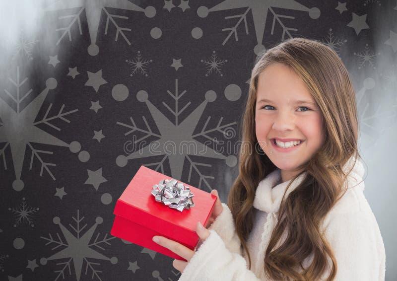 Menina contra o fundo cinzento com testes padrões do presente e do floco de neve do Natal imagem de stock