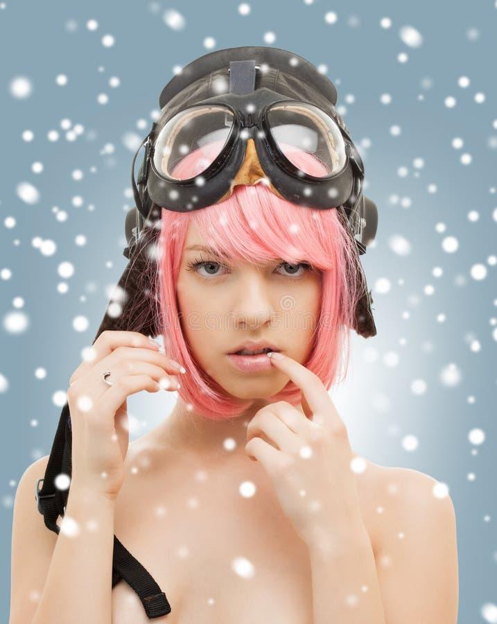Menina cor-de-rosa do cabelo no capacete do aviador com neve fotografia de stock