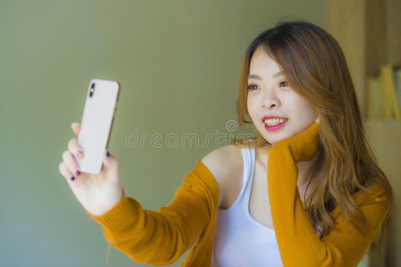 Menina coreana asiática atrativa e relaxado nova que usa o quarto do telefone celular em casa que aprecia o app datando em linha  foto de stock