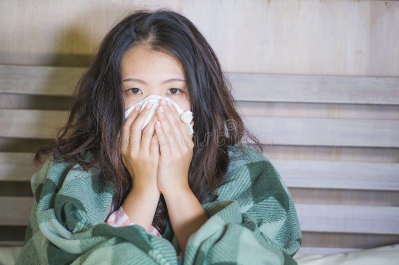 Menina coreana asiática doce nos pijamas cobertos com o frio doente e a gripe de sofrimento da cobertura que tomam a temperatura  imagem de stock royalty free