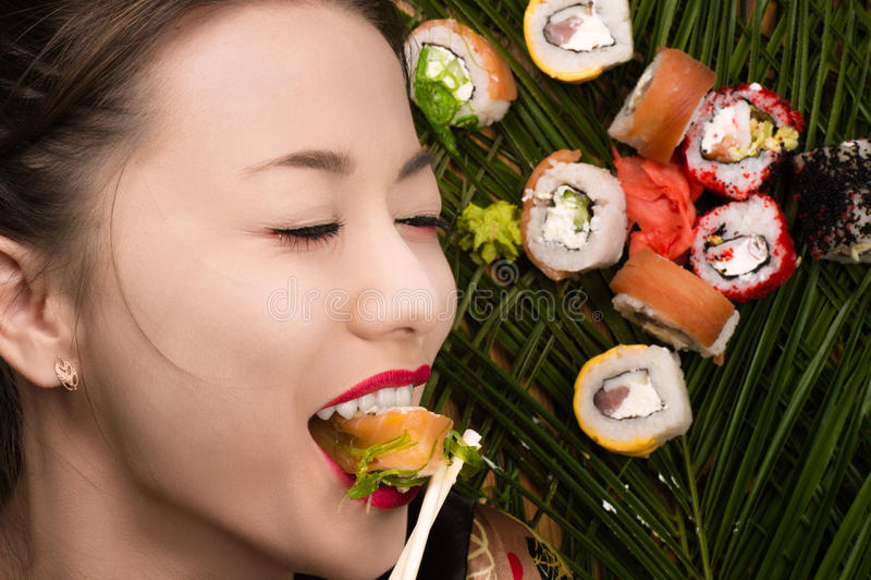 Menina coreana nova de sorriso que come rolos de sushi imagem de stock