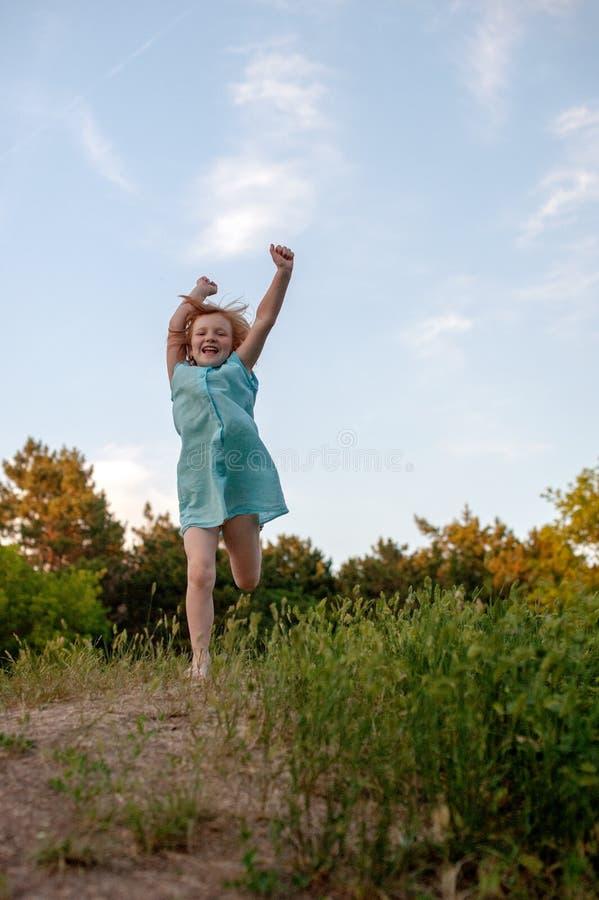 A menina corre alegremente com suas mãos acima fotos de stock royalty free