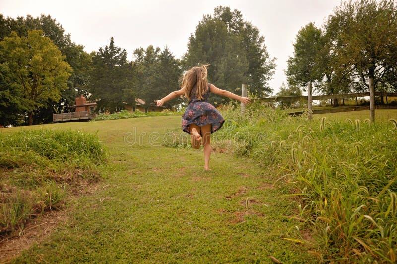 A menina corre na exploração agrícola a sua casa fotografia de stock royalty free