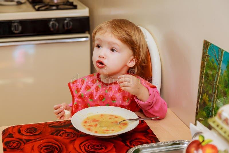a Menina-criança em idade pré-escolar come uma refeição saboroso em acolhedor imagem de stock