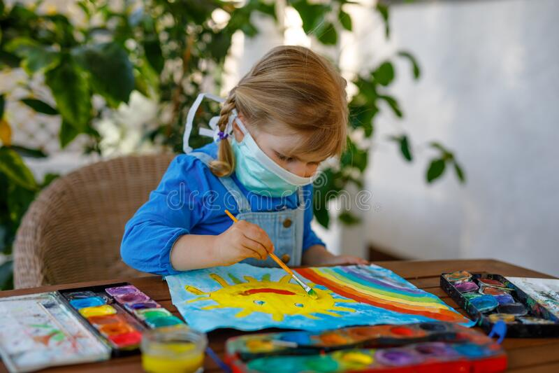 Menina criança em máscara médica pintando arco-íris com água durante a pandemia de quarentena de coronavírus fotos de stock royalty free