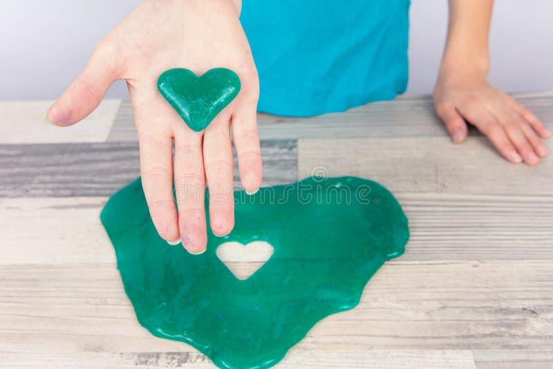 A menina criou um limo da forma do coração com um cortador e mostrá-lo da cookie em sua palma fotografia de stock royalty free