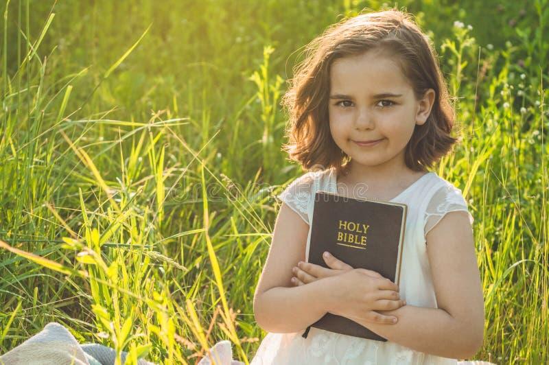 A menina cristã guarda a Bíblia em suas mãos Lendo a Bíblia Sagrada em um campo durante o por do sol bonito Conceito para a fé foto de stock royalty free