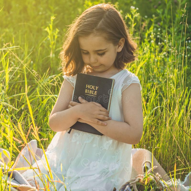 A menina cristã guarda a Bíblia em suas mãos Lendo a Bíblia Sagrada em um campo durante o por do sol bonito Conceito para a fé imagem de stock
