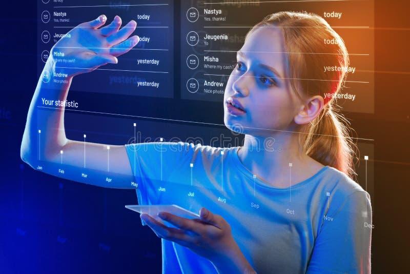 Menina cuidadosa que toca na tela transparente ao guardar um smartphone fotos de stock royalty free