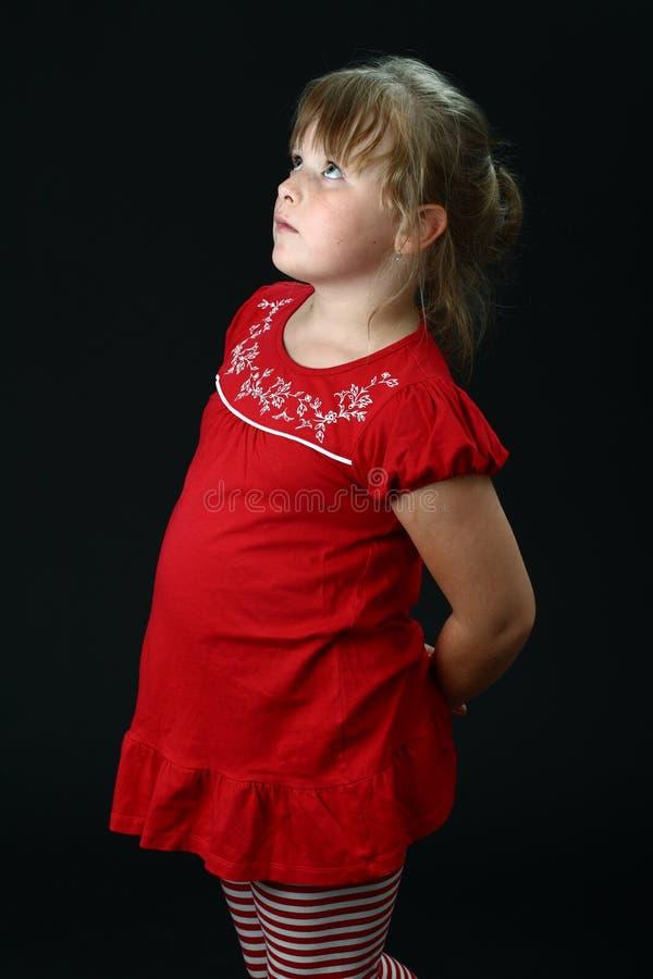 A menina culpada olha acima com mãos atrás dela para trás imagens de stock royalty free