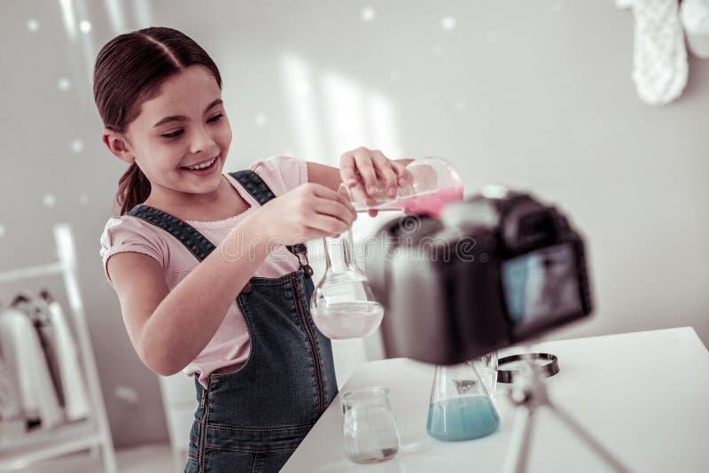 Menina curiosa alegre que está sendo interessada na química imagem de stock