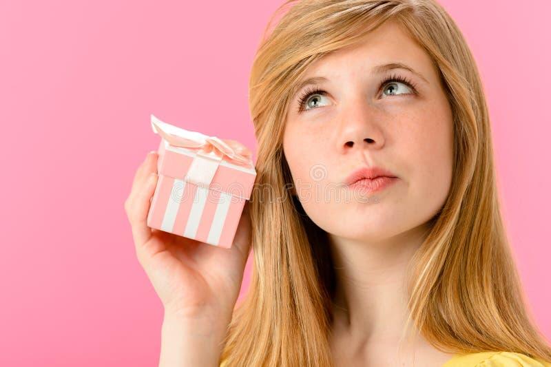 Menina curiosa que guardara presente fechado fotografia de stock royalty free