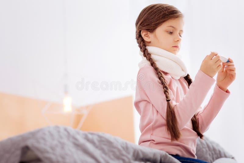 Menina curiosa que mede a temperatura ao sentar-se na cama fotografia de stock