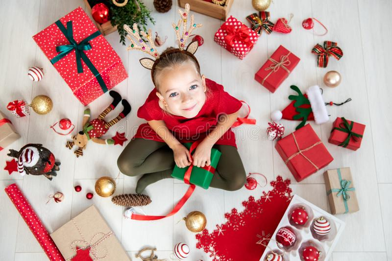 Menina curiosa que veste os chifres da rena do traje do xmas que sentam-se no assoalho, presente de Natal de abertura, vista supe fotografia de stock royalty free