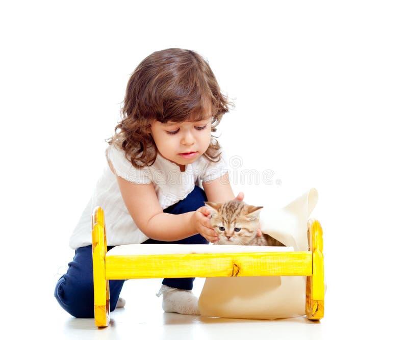 Menina Curly da criança que joga com gatinho fotografia de stock royalty free