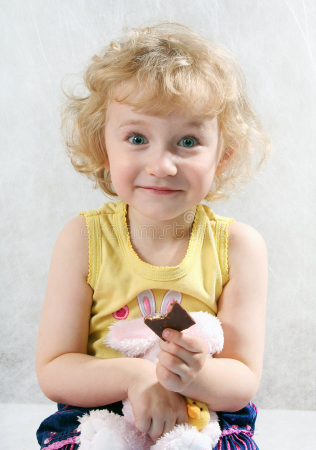 Menina curly loura pequena que come o chocolate imagens de stock royalty free