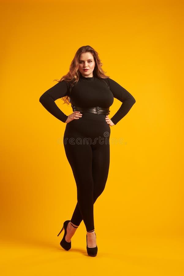 Menina curvy bonita na roupa 'sexy' que levanta no estúdio imagem de stock