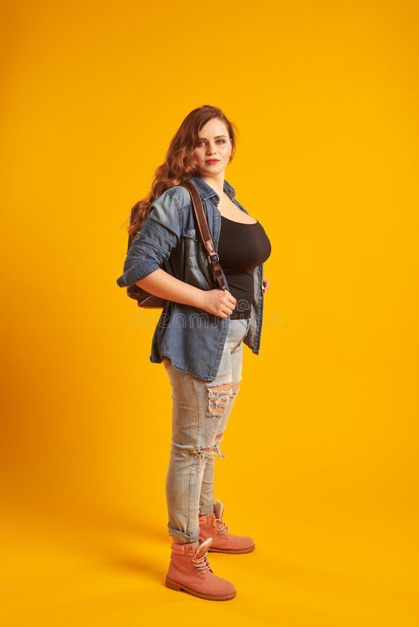 Menina curvy segura no revestimento da sarja de Nimes com a trouxa que olha o Ca foto de stock