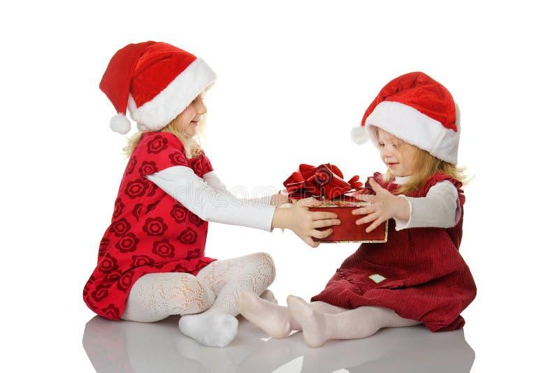 A menina dá à irmã um presente. foto de stock royalty free