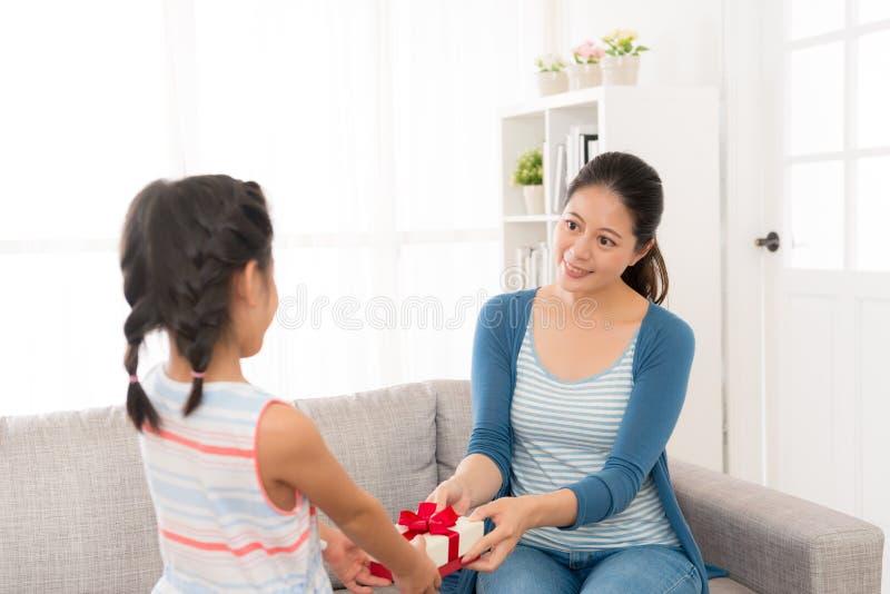 A menina dá a sua mãe nova uma caixa de presente vermelha imagem de stock royalty free