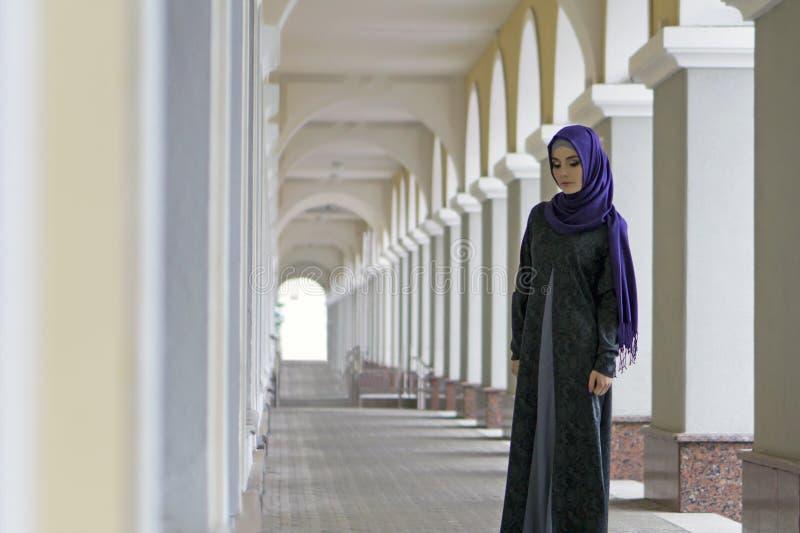 Menina da aparência do Oriente Médio na roupa muçulmana que está na galeria da cidade fotos de stock royalty free
