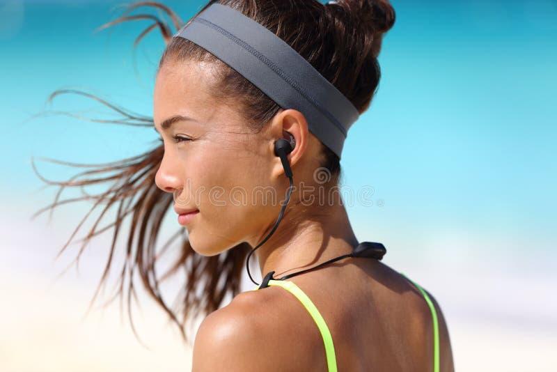 Menina da aptidão com os fones de ouvido do rádio da em-orelha do esporte fotografia de stock